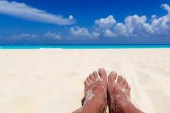 Лето и концепция пляжа - ноги человека на тропическом пляже приставают к берегу Стоковое Изображение