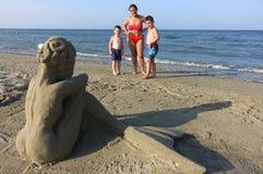 Лето: мать и 2 дет смотрят скульптуру песка на пляже Стоковое Фото