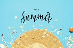 Лето надписи здравствуйте Положение концепции летних каникулов плоское Шляпа и seashells на голубой предпосылке стоковая фотография rf