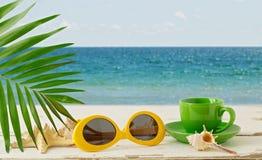 лето неба seascape моря голубых утесов Ослабьте на пляже, чашке кофе и sunglas Стоковое Изображение