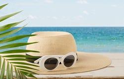 лето неба seascape моря голубых утесов Ослабьте на пляже, шляпе и белых солнечных очках Стоковая Фотография RF