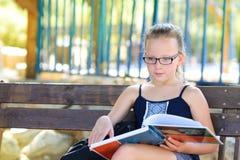 Лето ослабляя - книга чтения маленькой девочки на открытом воздухе на теплый день стоковые изображения rf