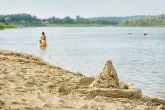 Лето, пляж, замок песка на береге, запачкало людей в озере Стоковое Фото