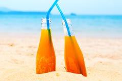 Лето предпосылки моря 2 бутылок апельсинового сока Стоковые Фото