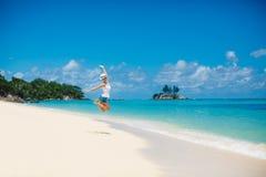 Лето, смеясь над женщина скача на пляж Стоковая Фотография