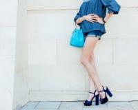 Лето Способ Leggy молодая женщина представляя в обмундировании джинсовой ткани и модной сумке Стоковое Фото