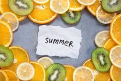 Лето - слово с тропическими плодоовощами на серой предпосылке Стоковое фото RF