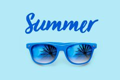 Лето текстурировало голубой текст и голубые солнечные очки с отражениями пальм изолированные в свете - голубой предпосылке стоковое фото