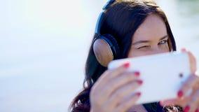 Лето, outdoors, портрет красивой женщины, при длинные темные волосы, слушая к музыке на наушниках от черни сток-видео