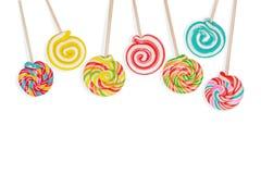 Леденец на палочке конфеты радуги на ручке изолированной в белизне Стоковые Фото