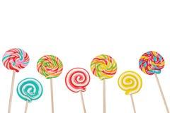 Леденец на палочке конфеты радуги на ручке изолированной в белизне Стоковое Изображение