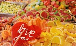Леденец на палочке с влюбленностью вы слова и кучи покрашенных конфет как предпосылка Стоковое фото RF