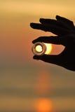 Лед и заход солнца владением руки силуэта круглый стоковые фотографии rf