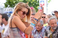 ЛЕ-МАН, ФРАНЦИЯ - 13-ОЕ ИЮНЯ 2014: Красивая девушка делает автопортрет на smartphone окруженном человеком Стоковое Изображение