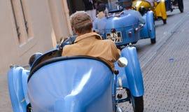 ЛЕ-МАН, ФРАНЦИЯ - 13-ОЕ ИЮНЯ 2014: Парад участвовать в гонке пилотов Пилот управляет ретро автомобилем Стоковые Изображения