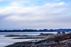 Ледовитая панорама фьорда с домами на каменистом береге тундры в a Стоковая Фотография RF
