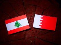 Ливанский флаг с бахрейнским флагом на пне дерева Стоковое Изображение