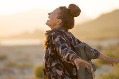 Ликование женщины против горы и ландшафта океана на заходе солнца стоковые изображения rf
