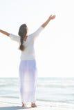 Ликование молодой женщины на морском побережье. вид сзади стоковая фотография
