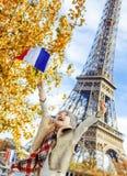 Ликование ребенка и поднимая флаг пока сидящ на парапете, Париже стоковое изображение rf
