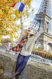 Ликование ребенка и поднимая флаг пока сидящ на парапете, Париже стоковые изображения rf