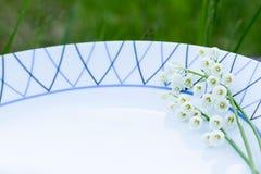 Лилии долины на белой плите меню против детенышей весны цветка принципиальной схемы предпосылки белых желтых Стоковые Фото