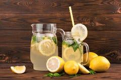 Лимонад питья лета с зрелыми лимонами, мятой, и льдом на темном деревянном столе Лимонад с свежими лимонами и зеленой мятой Стоковые Фотографии RF