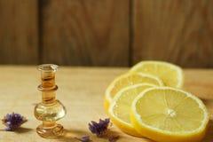 Лимонная кислота в бутылке на деревянном столе, рядом с лимоном, отрезала куски Стоковые Фотографии RF