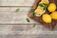 Лимоны на деревянной плите с космосом экземпляра стоковые изображения rf
