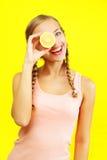 Лимоны удерживания девушки на желтой предпосылке Стоковое Изображение RF