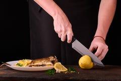 лимон вырезывания женщины для испеченных рыб на деревянной доске для блюда в кухне, взгляда конца-вверх рук Сваренные рыбы с лимо Стоковое фото RF