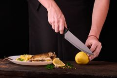 лимон вырезывания женщины для испеченных рыб на деревянной доске для блюда в кухне, взгляда конца-вверх рук Сваренные рыбы с лимо Стоковые Изображения RF