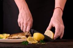 лимон вырезывания женщины для испеченных рыб на деревянной доске для блюда в кухне, взгляда конца-вверх рук Сваренные рыбы с лимо Стоковые Фотографии RF