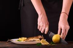 лимон вырезывания женщины для испеченных рыб на деревянной доске для блюда в кухне, взгляда конца-вверх рук Сваренные рыбы с лимо Стоковая Фотография