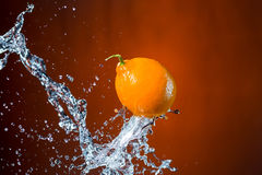 Лимон и выплеск воды на оранжевой предпосылке Стоковое Изображение RF