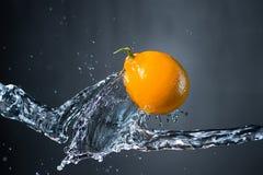 Лимон и выплеск воды на серой предпосылке Стоковые Изображения RF
