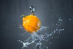 Лимон и выплеск воды на серой предпосылке Стоковые Фото