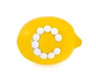 лимон c предпосылки над белизной витамина пилек Стоковые Фото