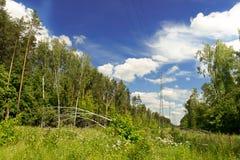 Линии электропередач в лесе, облаках и голубом небе, высоковольтных проводах стоковое изображение