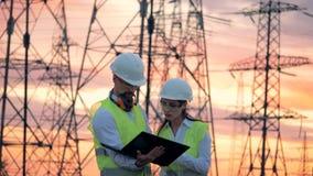 Линии электропередач и 2 инженера специалистов работая на развитии энергетики способном к возрождению во время захода солнца видеоматериал