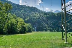 Линии электропередач и кабели электричества водя к горе встают на сторону при водопад символизируя гидроэлектрическую энергию стоковое фото rf