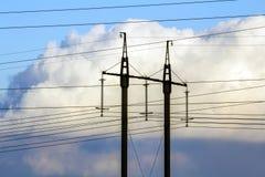 Линии электропередач передачи электричества против белых облаков высоко Стоковые Изображения RF