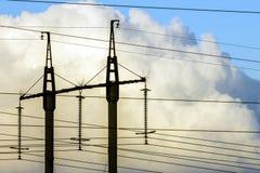 Линии электропередач передачи электричества против белых облаков высоко Стоковое Изображение RF