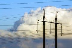 Линии электропередач передачи электричества против белых облаков высоко Стоковое Изображение