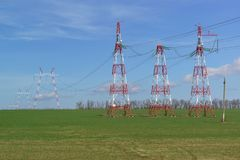 Линии электропередач поддержек в поле Красный и белый против яркого голубого неба Панели солнечных батарей для освещения безопасн стоковое фото