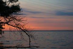 Линии электропередач против красивого захода солнца на воде Страна стоковая фотография rf