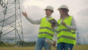 Линии электропередач, человек и инженеры женщины с планшетом в их руках обсуждая прогресс конструкции сток-видео
