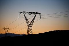 Линии электропередач с заходом солнца в предпосылке Стоковое Изображение RF