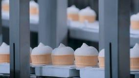 Линия автоматического производства мороженого - конвейерная лента с конусами мороженого видеоматериал