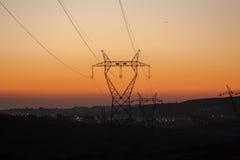Линия башни силы в открытом поле горящим небом Стоковые Фото